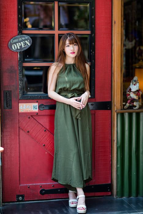 フリー写真 ドレス姿で店のドアの前に立つ女性の全身ショット