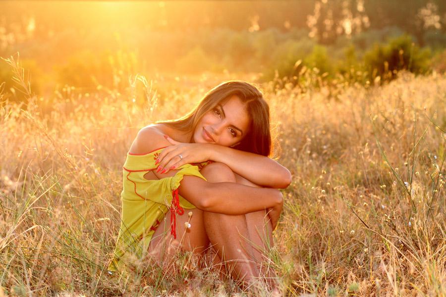 フリー写真 夕暮れの草むらで膝を抱える外国人女性
