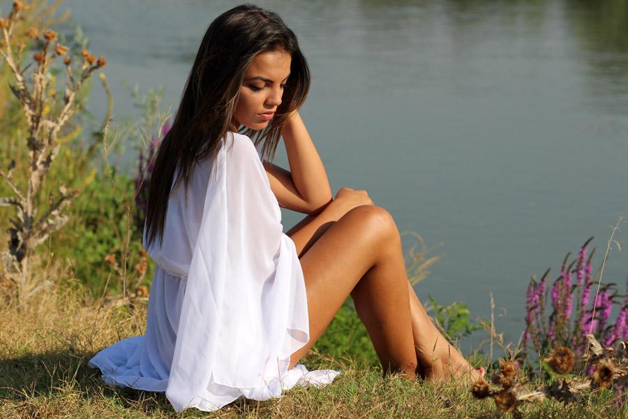 フリー写真 ドレス姿で湖の前に座る外国人女性