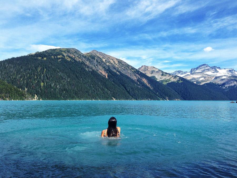 フリー写真 山と湖で泳ぐ女性の後ろ姿