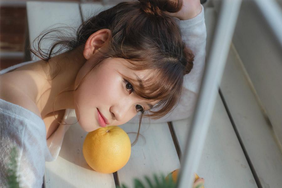 フリー写真 テーブルに置いたオレンジに頬をつける女性