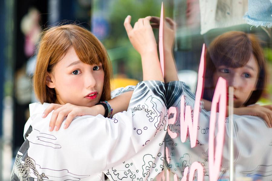 フリー写真 店のガラス窓によりかかる女性