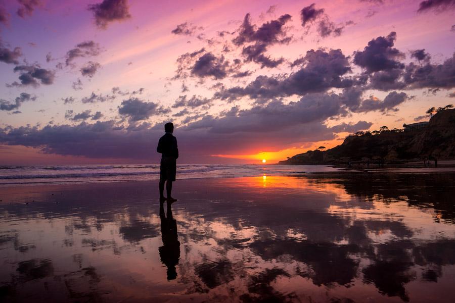 フリー写真 沈む太陽とビーチに立つ人物のシルエット