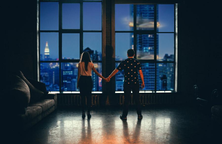 フリー写真 手をつないで爆破されるビルを眺めているカップル