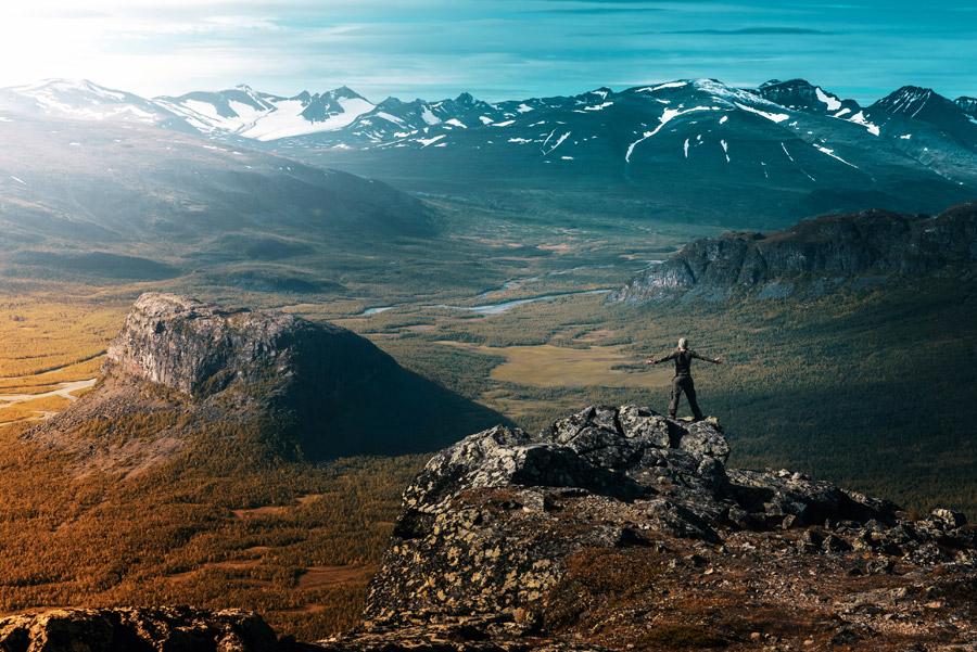 フリー写真 岩山の山頂に立って手を広げる人物