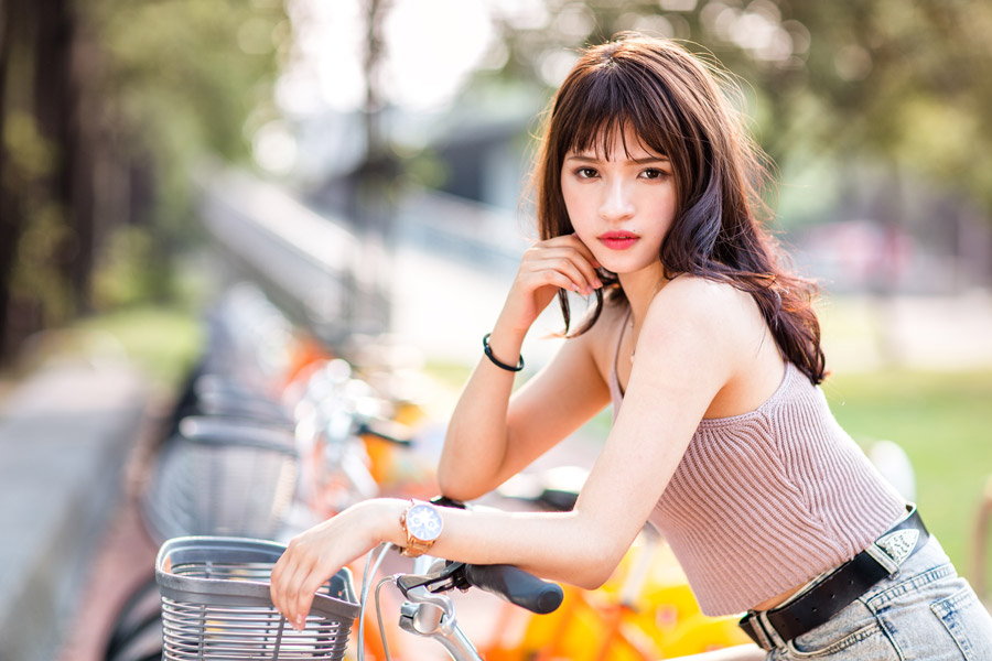 フリー写真 自転車に跨って顎に手を当てている女性