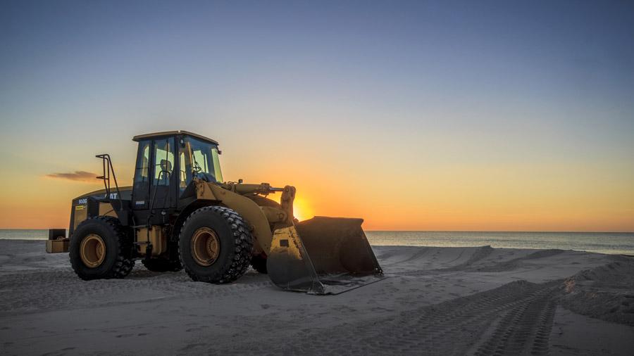 フリー写真 夕暮れのビーチとホイールローダー
