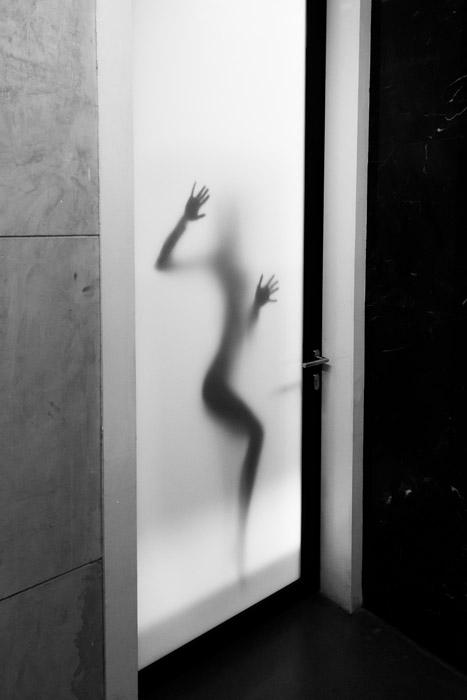 フリー写真 扉の向こうで手をつく女性の人影