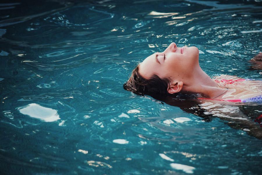 フリー写真 プールの水面に浮かぶ外国人女性