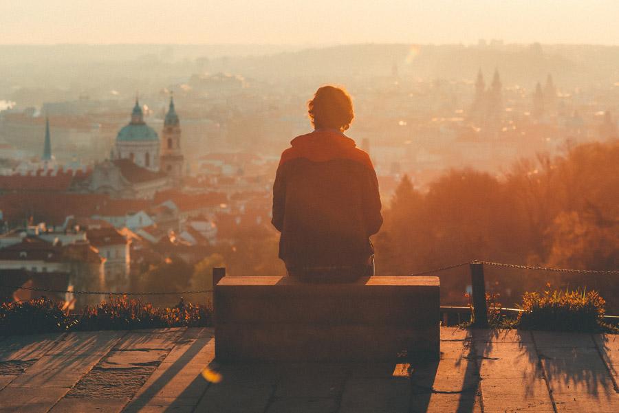 フリー写真 ベンチに座って夕暮れのプラハの街を眺める人物