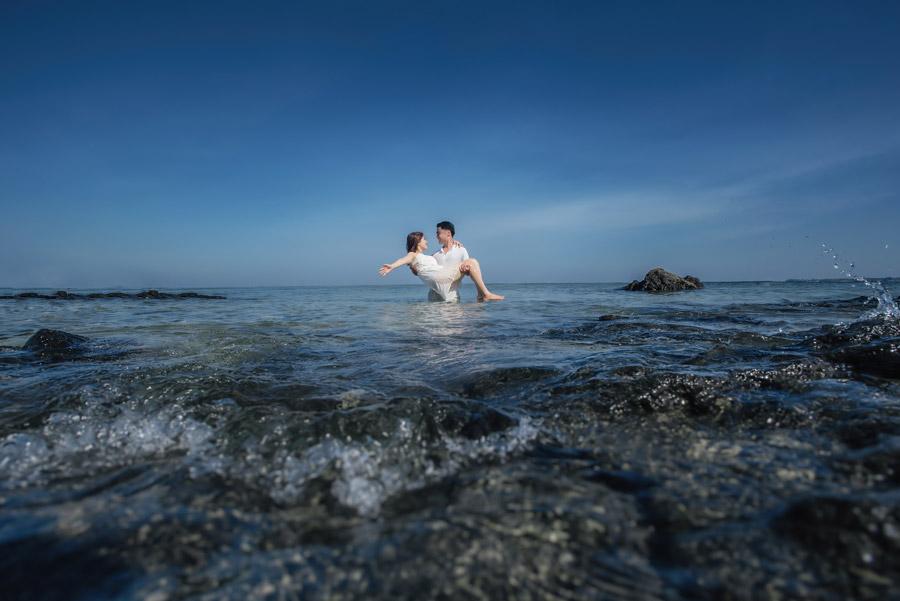 フリー写真 海に入って彼女を抱き上げる彼氏