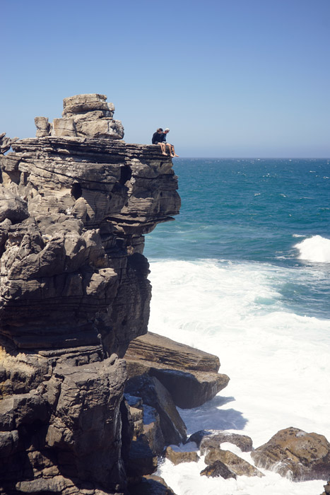 フリー写真 海岸の崖の上に座る二人の男性