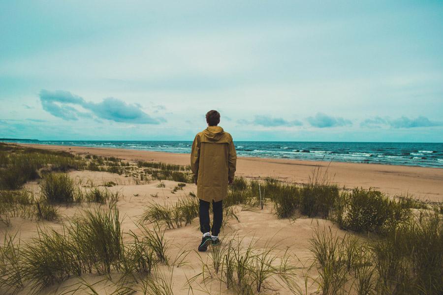 フリー写真 レインコート姿で浜辺を歩く男性の後ろ姿