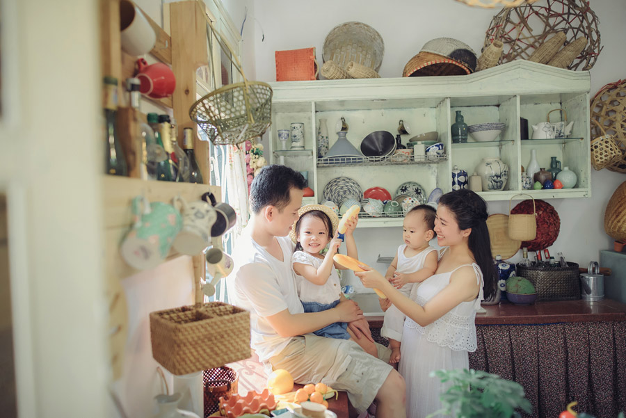 フリー写真 台所でパンを持った四人家族