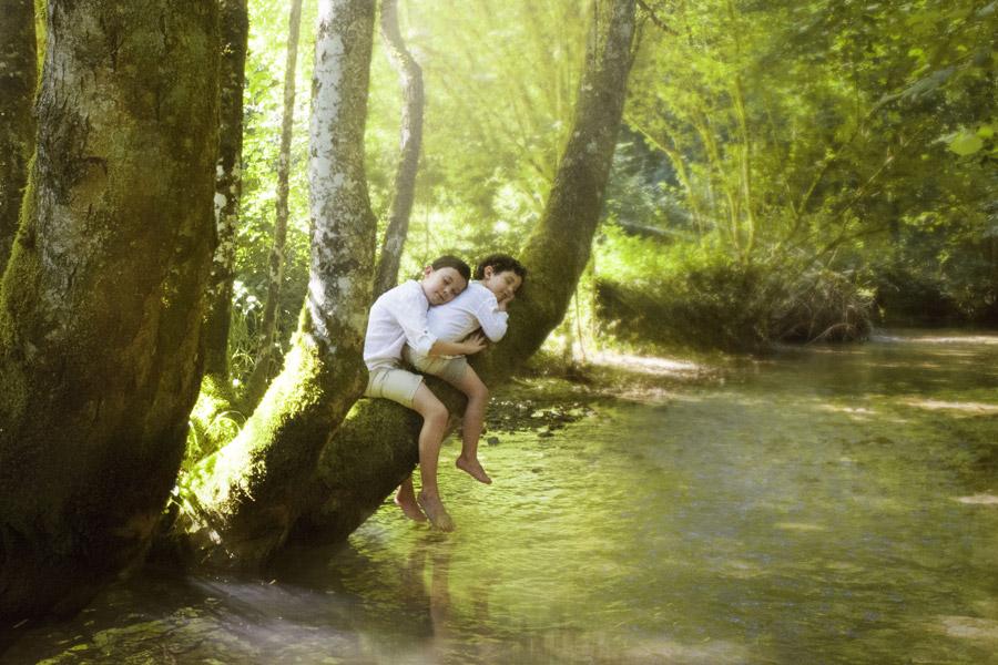 フリー写真 小川の上の木に跨って眠る子供たち
