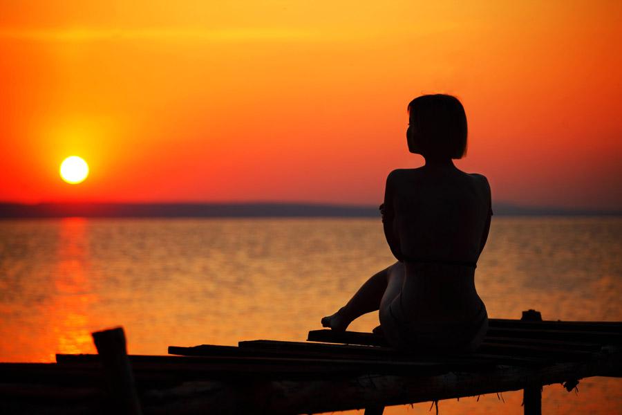 フリー写真 日の出の太陽と座っている女性のシルエット