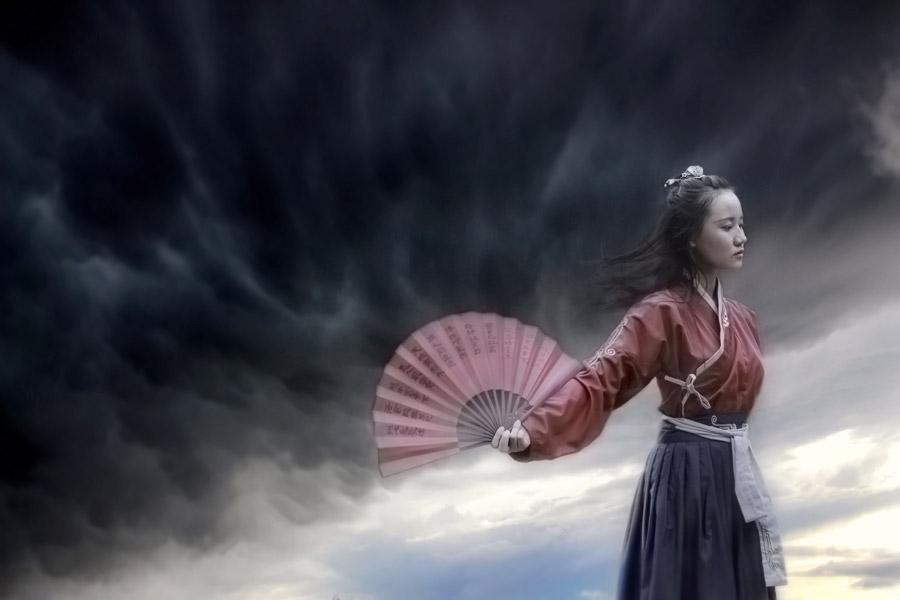 フリー写真 暗雲と漢服姿で扇子を広げる女性