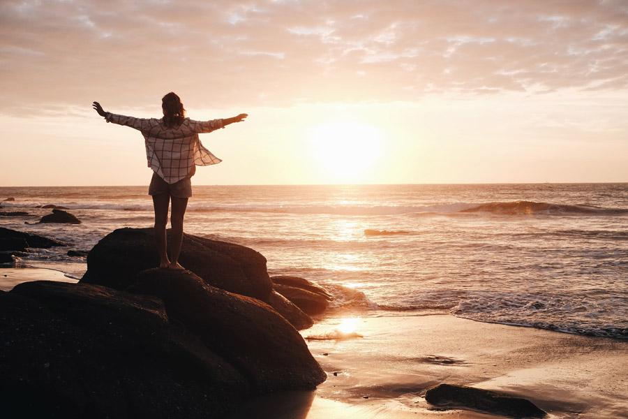 フリー写真 夕暮れの海と岩の上で手を広げる女性の後ろ姿