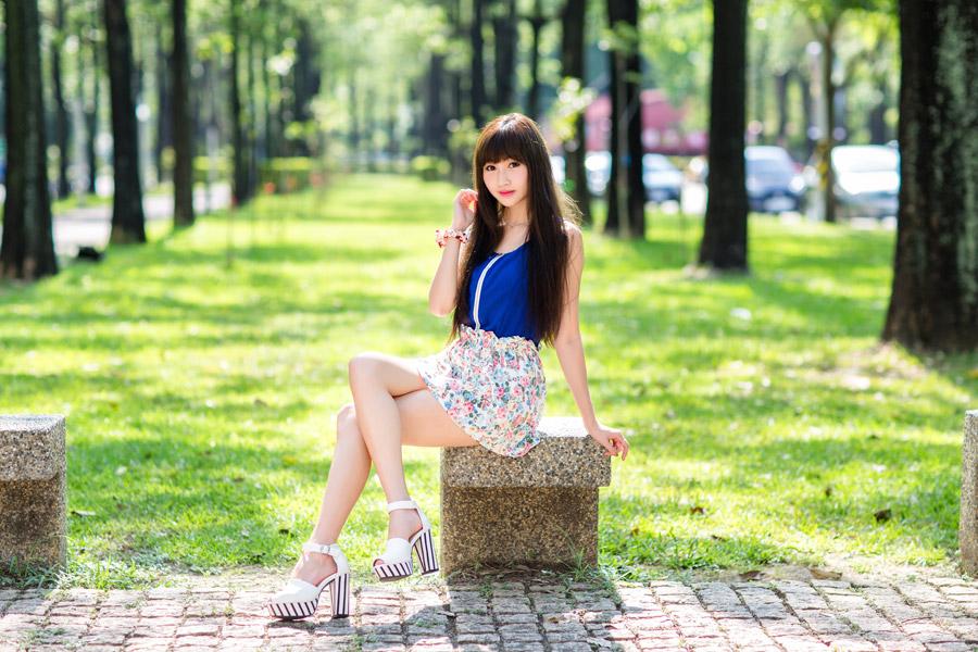 フリー写真 足を組んで石のベンチに座る女性