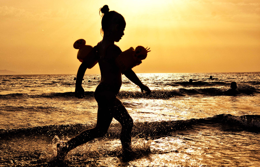 フリー写真 夕暮れの波打ち際を歩く女の子のシルエット