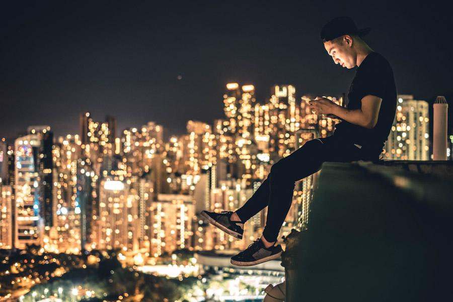フリー写真 香港の夜景と屋上でスマホをいじる男性