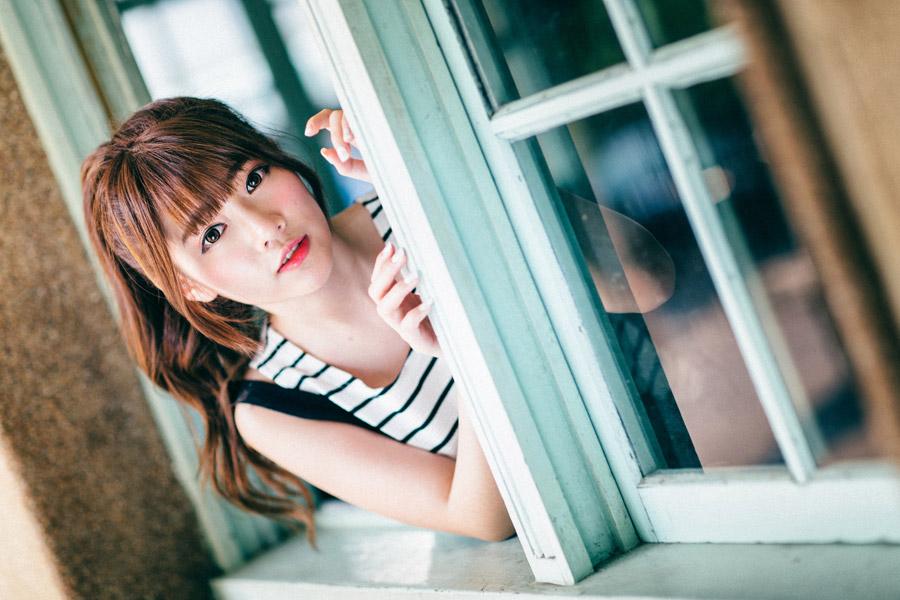 フリー写真 窓から身を乗り出す女性