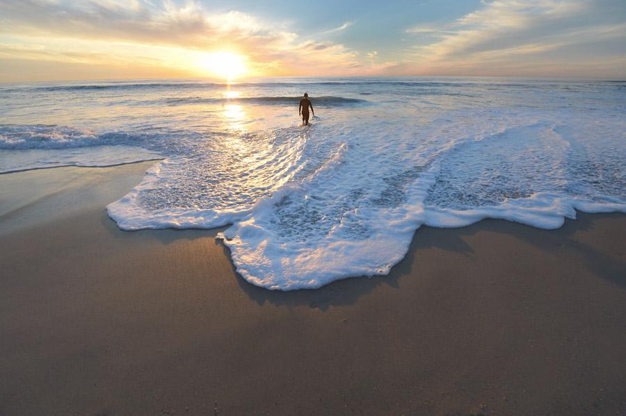 フリー写真 夕日と海に入る人物の後ろ姿