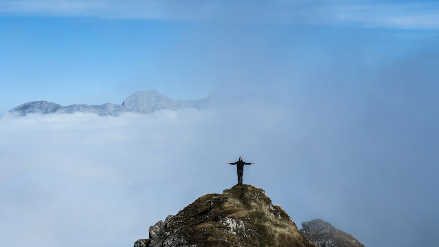 フリー写真 山の頂上に立って手を広げる人物
