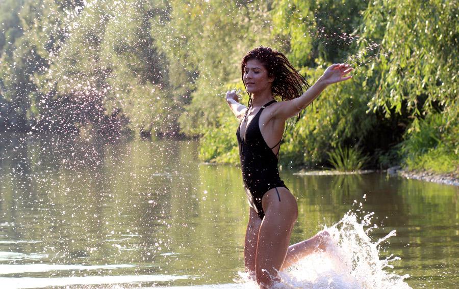 フリー写真 水しぶきを上げて川を走る外国人女性