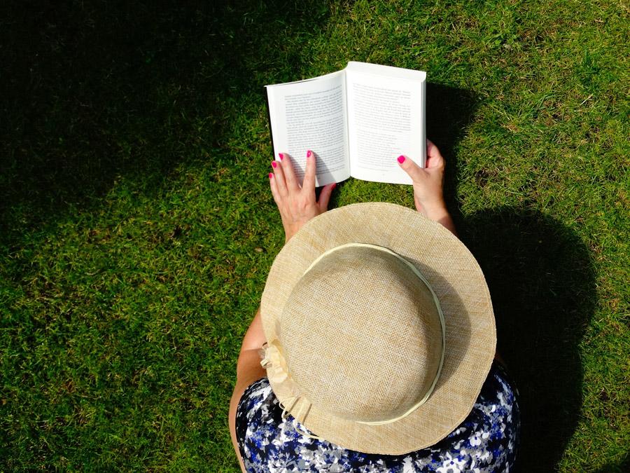 フリー写真 芝生の上で本を読んでいる女性