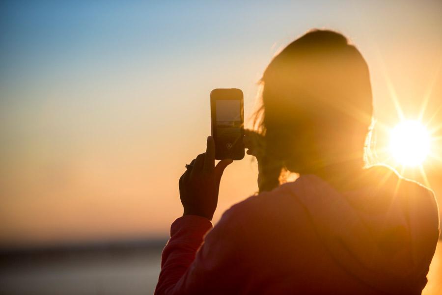 フリー写真 夕日とスマホで写真を撮る女性