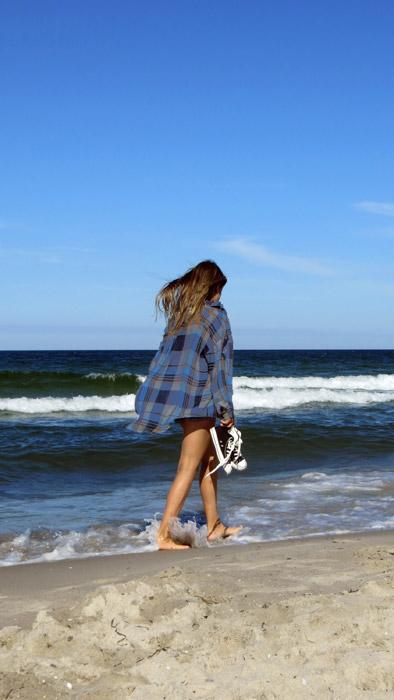 フリー写真 裸足で波打ち際を歩く女性