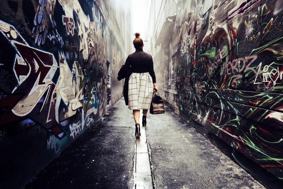 フリー写真 鞄を持って路地裏を歩く女性の後ろ姿