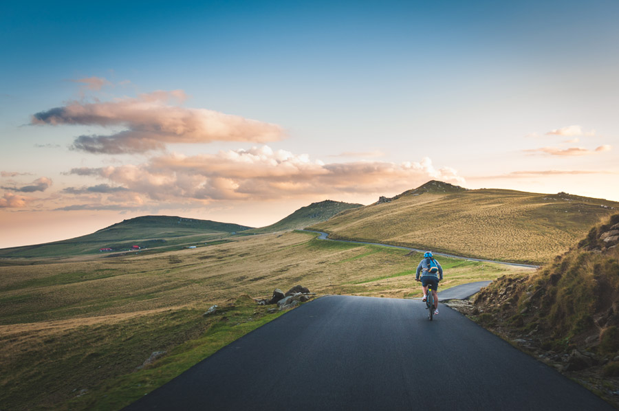 フリー写真 田舎道をサイクリングする人物