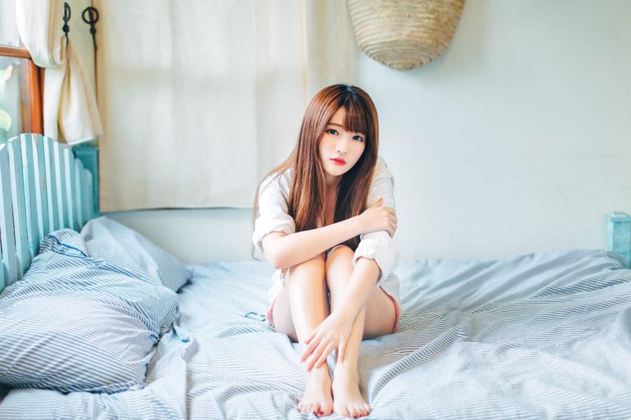 フリー写真 パジャマ姿でベッドの上に座る女性