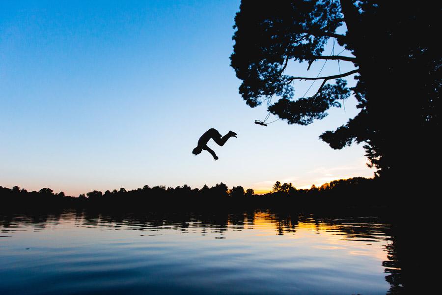フリー写真 夕暮れの湖に飛び込む人物のシルエット