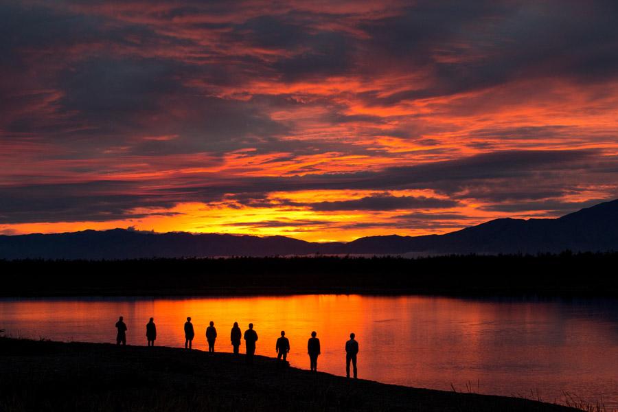 フリー写真 夕焼けと川の前に並ぶ人々のシルエット