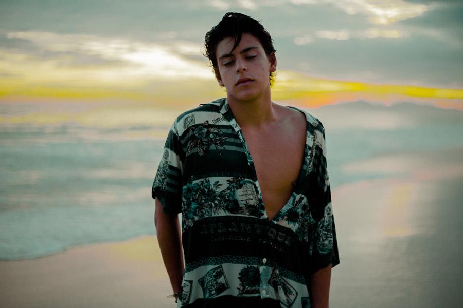 フリー写真 夕暮れのビーチと目を閉じる少年の
