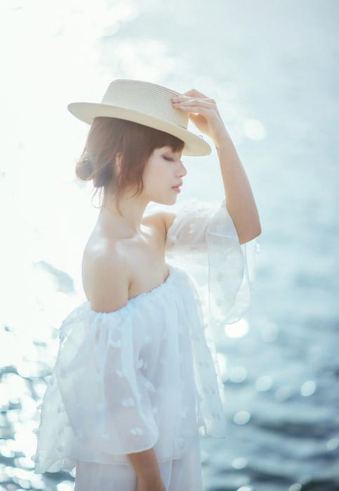 フリー写真 海と目を閉じながら帽子を被る女性