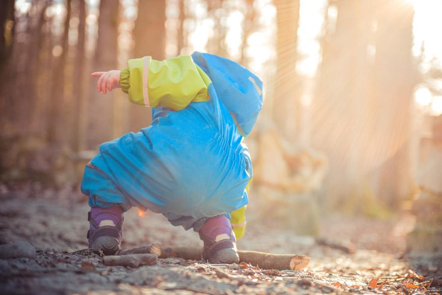 フリー写真 木の棒を拾う子供の後ろ姿
