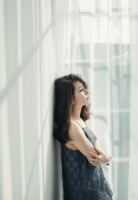 フリー写真 窓辺で腕を抱えている女性の横顔
