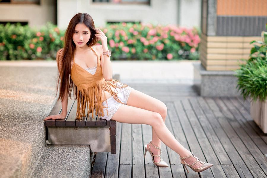 フリー写真 ベンチの上で横座りしている女性のポートレイト