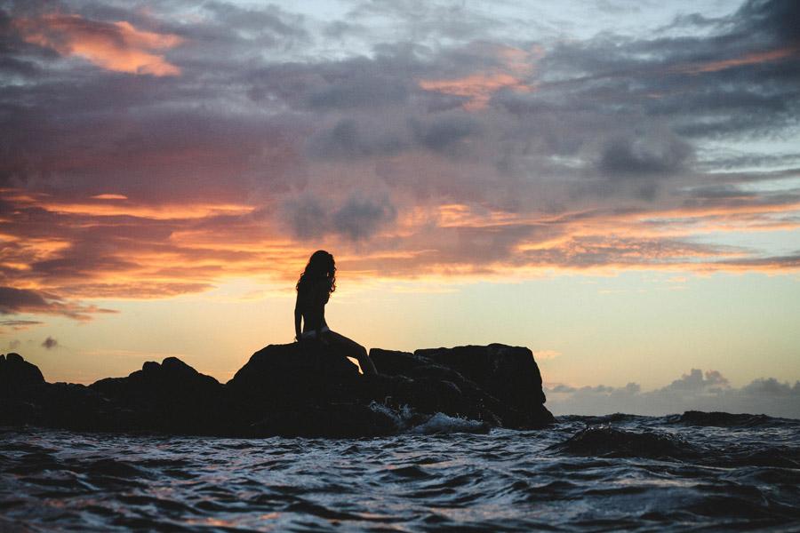 フリー写真 夕暮れの海岸の岩に座る女性