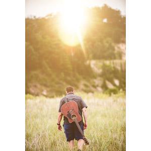フリー写真, 人物, 男性, 外国人男性, アメリカ人, 後ろ姿, 人と風景, 草むら, 太陽光(日光), 音楽, 楽器, 弦楽器, ギター, アコースティックギター