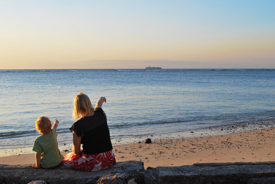 フリー写真 砂浜で船を指差す親子