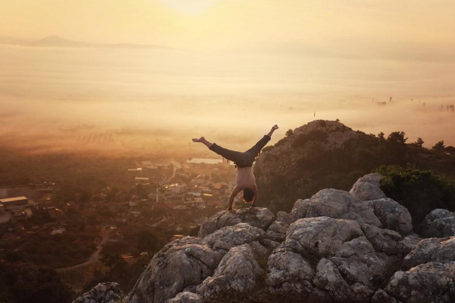 フリー写真 山の上の岩で逆立ちする男性と朝陽の風景