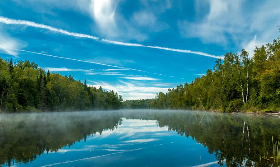 フリー写真 飛行機雲と青空が映る湖の風景