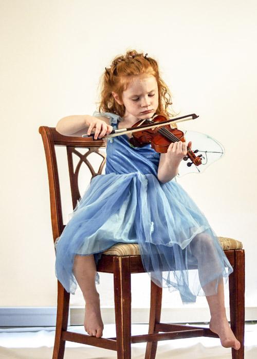 フリー写真 椅子に座ってバイオリンを弾く女の子