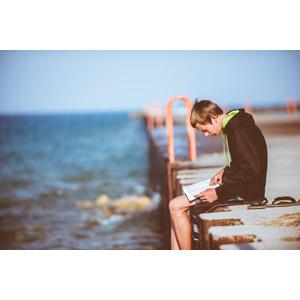 フリー写真, 人物, 少年, 外国の少年, 座る(地面), 読む(読書), アメリカ人, 人と風景, 堤防, 海, 本(書籍)