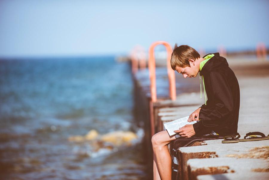 フリー写真 堤防で読書している外国の少年